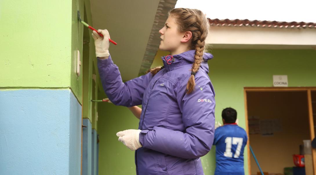 Como parte de su voluntariado para jóvenes en Perú, una adolescente pinta un muro en una primaria.